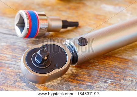 Torque wrench and spanner head on a wooden table in the workshop
