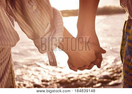 young couple lovers holding hands watching tide at beach.