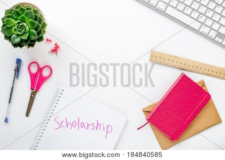 getting scholarship to bank card on white table background top view