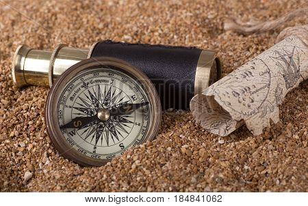 Brass compass and telescope with a treasure map on sand