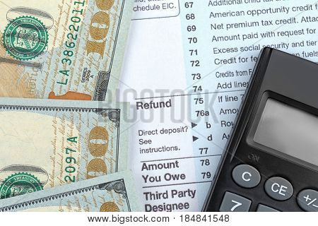 Tax refund document, calculator and dollars, closeup