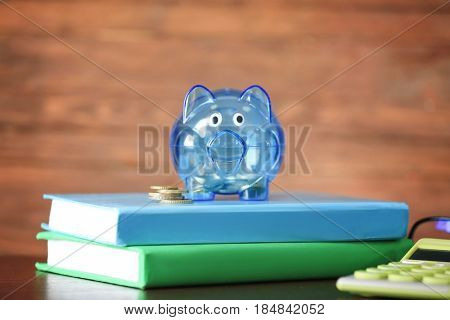 Composition of piggy bank with coins and notebooks on wooden table