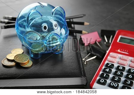 Composition of piggy bank with coins, stationery and calculator on grey table
