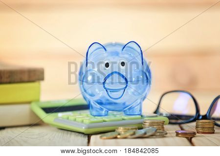 Composition of piggy bank, coins and calculator on wooden table