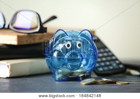 Piggy bank with coins on blurred background