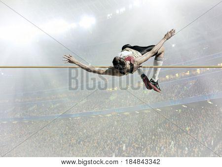 Athlete in action of high jump under stadium lights.