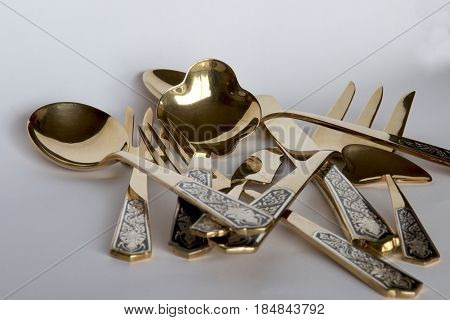A collection of gold Thai knives, forks and spoons.