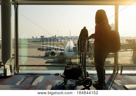 Young woman carrying a carry bag in airport terminal with airplane parking in airport runway in background.