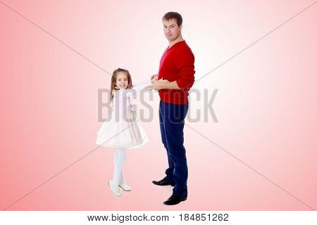 Cute little long-haired girl in a smart pink dress , reaches out to his dad.Pale pink gradient background.