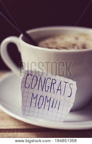 closeup of a piece of paper with the text congrats mom written in it, next to a cup with cappuccino