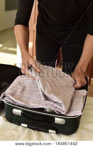 closeup of a young caucasian man putting clothes in his suitcase or putting them off, on the bed