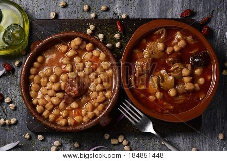 high-angle shot of two earthenware bowls with two typical spanish dishes, potaje de garbanzos, a chickpeas stew with chorizo and serrano ham on the left, and callos on the right, on a wooden table