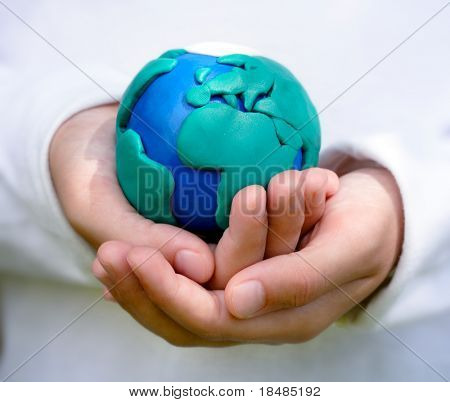 Hands of child holding colorful clay model of Planet Earth with African continent in foreground.