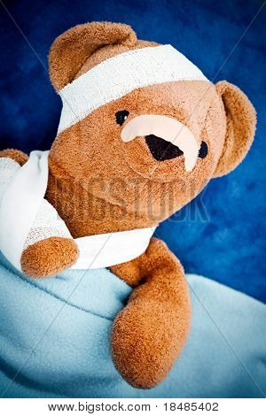 Sick teddy bear wrapped in bandages under blanket.