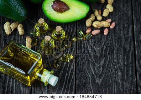 Oil of avocado with fish oil pills and peanut - source of omega 3 on a dark wooden background