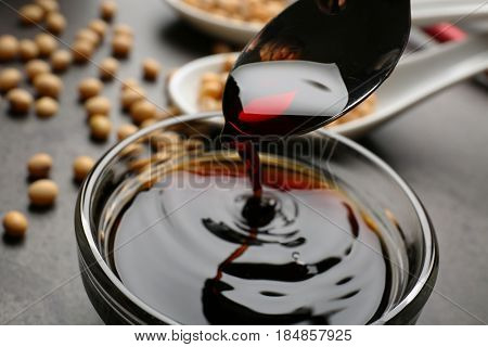 Bowl with tasty soy sauce and spoon on table, closeup