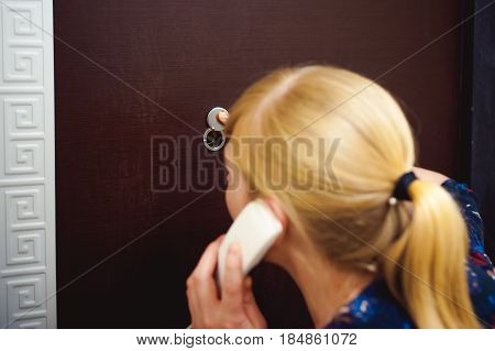 Blonde Woman Answers The Intercom Call, Hold The Phone To His Ear, Waiting For The Arrival Of The Lo
