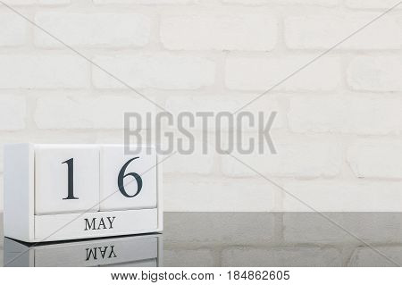 Closeup white wooden calendar with black 16 may word on black glass table and white brick wall textured background with copy space selective focus at the calendar