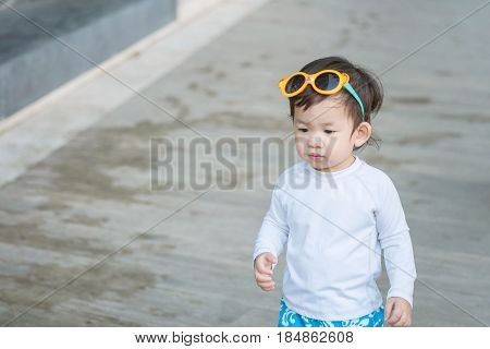 Closeup cute asian kid in swimming suit with sunglasses on his head in summer of thailand