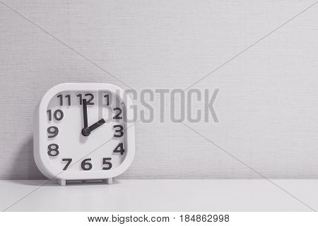 Closeup white clock for decorate in 2 o'clock on white wood desk and cream wallpaper textured background in black and white tone with copy space