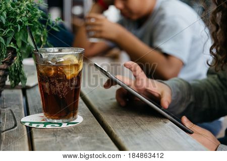 Refreshing glass of cola on wooden table in a bar while young is connected with tablet.
