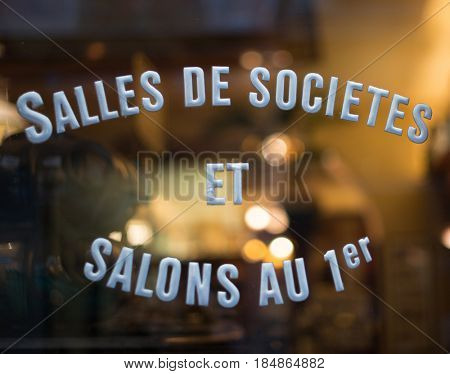 Old French bar with stenciled sign on window. Translation: meeting rooms on first floor