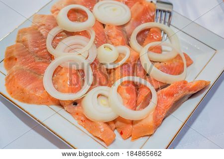 Closeup slices of red fish served with onion rings in restaurant