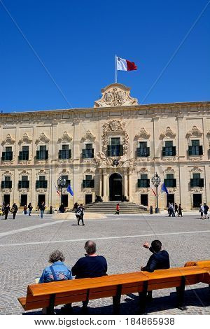 VALLETTA, MALTA - MARCH 30, 2017 - View of the Auberge de Castille (office of the Prime Minister) in Castille Square with tourists sitting on a bench in the foreground Valletta Malta Europe, March 30, 2017.