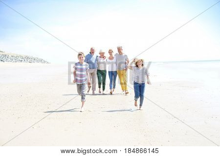 Family, parents, grandparents and grandkids walking on the beach poster