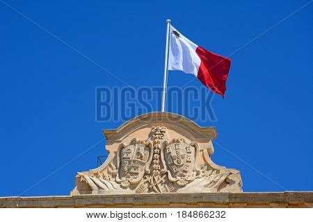 The coat of arms of Castille and Leon and Maltese flag on top of the Auberge de Castille (office of the Prime Minister) in Castille Square Valletta Malta Europe.