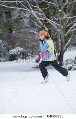 Mixed race girl running in snow