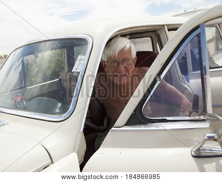 Senior Caucasian man getting out of vintage car