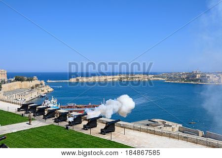 VALLETTA, MALTA - MARCH 30, 2017 - The Noon Gun in the Saluting Battery seen from the Upper Barrakka Gardens with views over the bay towards Fort Rikasoli Valletta Malta, March 30, 2017.