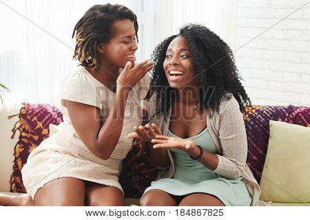 Pretty cheerful young women gossiping at home
