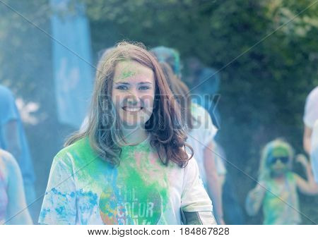 STOCKHOLM SWEDEN - MAY 22 2016: Waving smiling young beautiful woman covered with color dust in the Color Run Event in Sweden May 22 2016