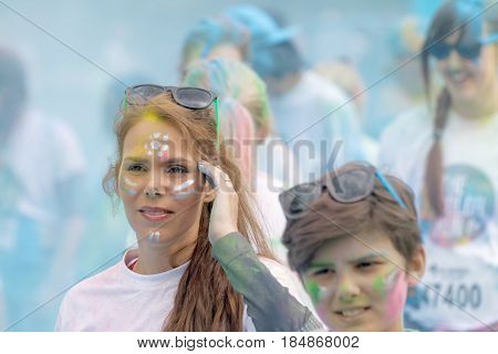 STOCKHOLM SWEDEN - MAY 22 2016: Teenager covered with color dust and makeup blue background in the Color Run Event in Sweden May 22 2016