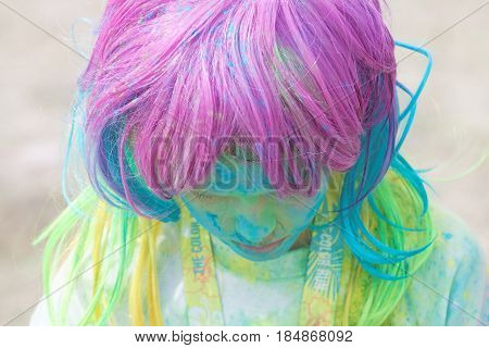 STOCKHOLM SWEDEN - MAY 22 2016: Girl with colorful wig covered with color dust looking down in the Color Run Event in Sweden May 22 2016
