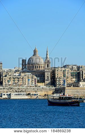VALLETTA, MALTA - MARCH 30, 2017 - View of Valletta city buildings and waterfront seen from Marsamxett Harbour with a tour boat in the foreground Valletta Malta Europe, March 30, 2017.