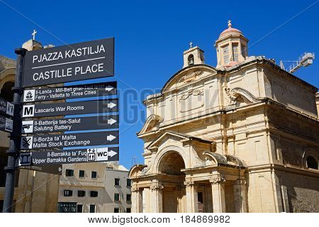 VALLETTA, MALTA - MARCH 30, 2017 - Castille Place signpost with St Catherine of Italy church to the rear in Castille Place Valletta Malta Europe, March 30, 2017.
