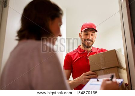 delivery, mail, people and shipping concept - happy man with clipboard delivering parcel boxes to customer signing form at home