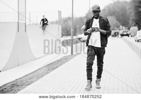Portrait Of Stylish African American Man On Sportswear, Cap And Glasses Looking On His Phone. Black