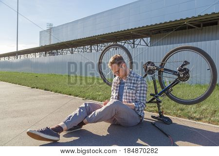 Upset man searches solution of a bicycle malfunction