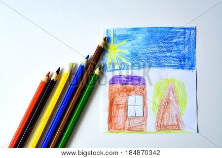 A child's drawing of house tree and sky colored pencils
