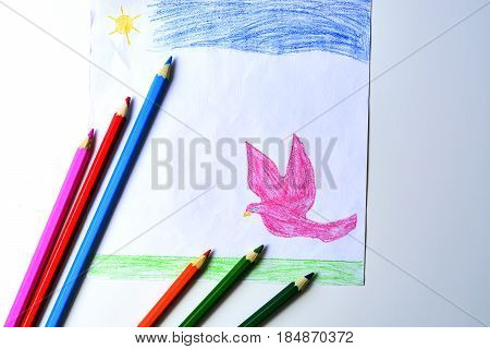 A child's drawing of a pink dove grass and sky with colored pencils.