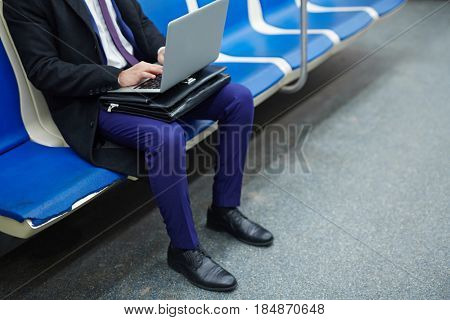 Low section portrait of unrecognizable man using laptop computer in subway train, working