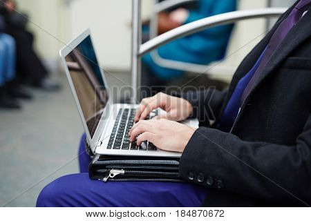 Side view portrait of unrecognizable businessman using laptop computer for work during subway ride