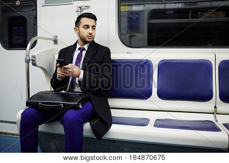 Portrait of young Middle-Eastern businessman commuting to work in subway train, using smartphone to listen to music