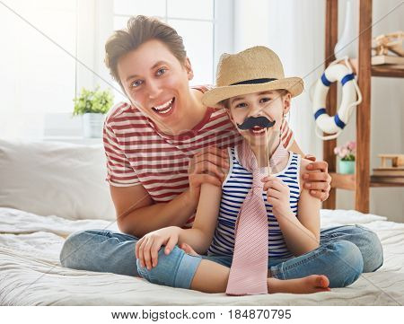 Funny time. Happy father's day! Dad and his child daughter are playing at home. Cute girl is holding paper mustache on stick and pretending of daddy. Family holiday and togetherness.