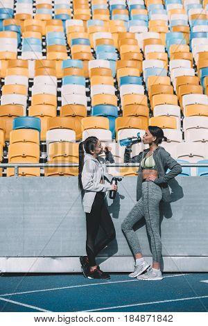 Smiling Young Sportswomen Drinking Water Near Stadium Seats
