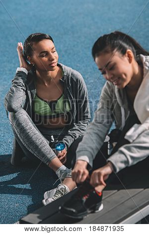 Tired Young Sportswomen Resting Together On Running Track Stadium